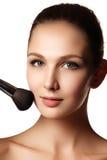 Skönhetflicka med makeupborstar Naturligt smink för brunetten Wo royaltyfria foton