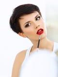 Skönhetflicka med makeupborsten. Naturligt smink för brunettkvinna med röda kanter royaltyfri fotografi