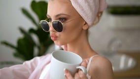 Skönhetflicka med vitt hår som hemma ser kameran Morgonfrukost med en kopp kaffe Modellen fotograferas stock video