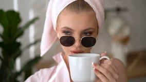Skönhetflicka med vitt hår som hemma ser kameran Morgonfrukost med en kopp kaffe Modellen fotograferas lager videofilmer