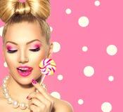 Skönhetflicka som äter den färgglade klubban arkivfoton