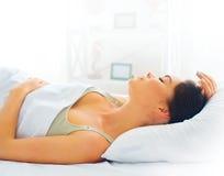 Skönhetflicka som sover i hennes bekväma säng Fotografering för Bildbyråer