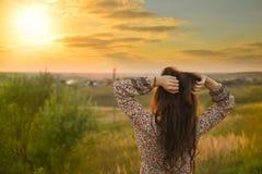 Skönhetflicka som tycker om utomhus naturen Härlig modell med lång sund blåsa hårspring på vårfältet, sol Royaltyfria Bilder