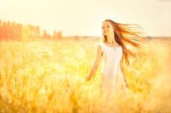 Skönhetflicka som tycker om utomhus naturen Härlig tonårs- modellflicka med sunt långt hår i den vita klänningen arkivbild