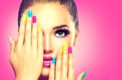 Skönhetflickaframsida med färgrikt nailpolish royaltyfria foton
