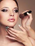 Skönhetflickamakeup cosmetic applicera smink härlig framsidakvinna Fotografering för Bildbyråer