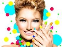 Skönhetflickan med färgrik makeup, spikar polermedel Arkivfoton