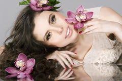 Skönhetflickan med Flowers.Beautiful modellerar kvinnan vänder mot. Fotografering för Bildbyråer