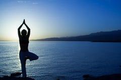 Skönhetflickan på stranden i yoga poserar, kopplar av konturn Royaltyfri Fotografi