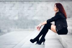 Skönhetflickan sitter på konkreta moment Royaltyfri Foto
