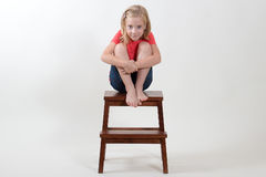 Skönhetflickasammanträde på en stol arkivfoton