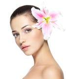 Skönhetframsida av den unga kvinnan med blomman Royaltyfri Foto