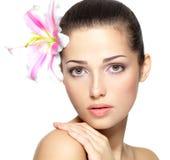 Skönhetframsida av kvinnan med blomman. Skönhetbehandling Royaltyfri Foto
