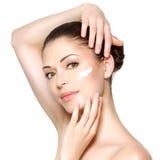 Skönhetframsida av kvinnan med skönhetsmedelkräm på framsida Arkivbild