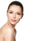 Skönhetframsida av kvinnan med skönhetsmedelkräm på framsida Arkivfoton