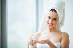 Skönhetframsidaomsorg Kvinna som applicerar kräm på hud arkivfoto