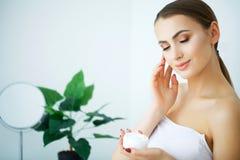 Skönhethudomsorg Härlig kvinna som applicerar kosmetisk framsidakräm royaltyfria foton