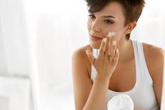 Skönhethudomsorg Härlig kvinna som applicerar kosmetisk framsidakräm Arkivfoto