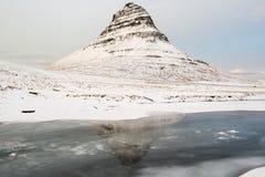 SkönhetKirkjufell berg med vattenreflexion på vintern, Island Arkivbild