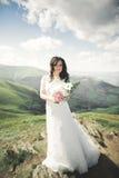 Skönhetkvinna, brud med den perfekta vita klänningen som poserar på vaggabakgrundsbergen fotografering för bildbyråer