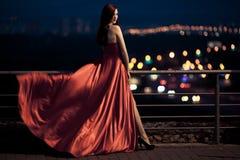 Skönhetkvinna i den utomhus- fladdrande röda klänningen royaltyfria bilder