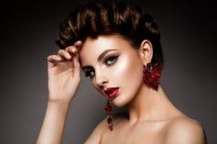 Skönhetkvinna med blåa ögon och röda kanter arkivfoton