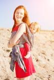 Skönhetkvinna med en behandla som ett barn i en rem behandla som ett barn momen Moder och ch Arkivfoton