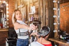 Skönhetkvinna med långt sunt och skinande slätt svart hår Frisören gör håromsorg till klienten nära spegeln arkivbild
