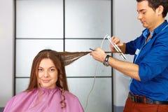 Skönhetkvinna med långt sunt och skinande slätt svart hår Kvinnafrisyr Bruk av straighteneren arkivfoto