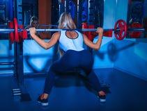 Skönhetkvinna med skivstången i idrottshall Arkivfoton