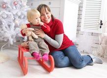 Skönhetkvinna och barn inomhus på pulkan på julgarnering med xmas-text Royaltyfri Bild