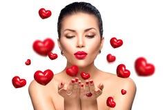 Skönhetkvinna som blåser valentinhjärtor Fotografering för Bildbyråer