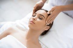 Skönhetkvinna som får ansikts- massage arkivbild