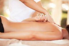 Skönhetkvinna som får ansikts- massage Avkopplad le kvinna som mottar en tillbaka massage royaltyfri bild