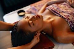 Skönhetkvinna som får ansikts- massage Händer som masserar kvinnahuvudet på den thailändska skönhetsalongen arkivfoto