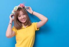 Skönhetkvinna som framme poserar med blommahatten av blå väggbackgr royaltyfria foton
