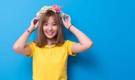Skönhetkvinna som framme poserar med blommahatten av blå väggbackgr royaltyfri fotografi