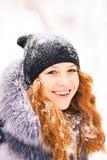 Skönhetkvinna som har den roliga yttersidan i trä på snöig dag för vinter Arkivbild