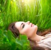 Skönhetkvinna som ligger på fältet i grönt gräs Royaltyfri Bild