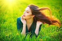 Skönhetkvinna som ligger på fältet som tycker om naturen Härlig brunettflicka med sunt långt flyghår fotografering för bildbyråer