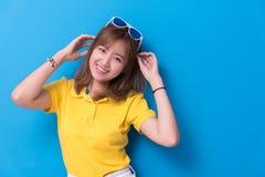 Skönhetkvinna som poserar med solglasögon som är främst av blå väggbackgr royaltyfria bilder