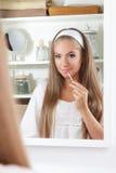 Skönhetkvinna som sätter på lipgloss royaltyfri bild