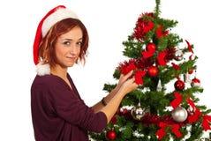 Skönhetkvinnan dekorerar julgranen Arkivbild