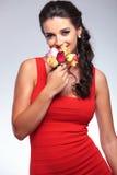 Skönhetkvinnan luktar några blommor i studio Arkivfoto