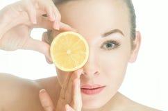 Skönhetkvinnan ser fotografen till och med en skiva av citronen Royaltyfri Bild