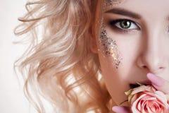 Skönhetkvinnastående den halva framsidan av den unga lockiga blonda kvinnan med pastellfärgad manikyr och det perfekta konstsmink Royaltyfri Foto
