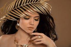 Skönhetmakeup i guld Modebrunettflicka med långt krabbt hår royaltyfria foton