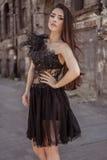 Skönhetmodekvinna som bär den märkes- stilfulla klänningen i den abadoned staden Arkivbilder