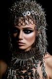 Skönhetmodell för högt mode med metallisk headwear- och mörkermakeup och blåa ögon på svart bakgrund arkivbild