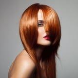 Skönhetmodell med perfekt långt glansigt rött hår royaltyfria bilder